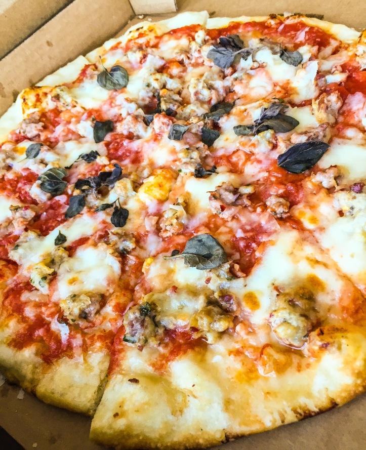 Pizza made with garlic oil, san marzano tomato sauce, Una's meatball mix, trecce cheese, and grana padano.